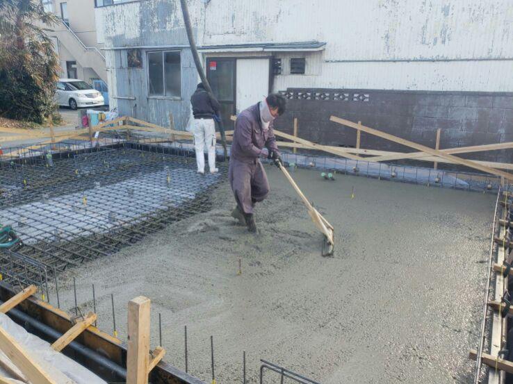 耐圧盤のコンクリート打ち込みが始まりです。基礎屋さんが手に持っている木の棒、通称「とんぼ」。とんぼを使ってコンクリートを均一に均していきます。